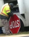 City employee fixing the stop sign on the spot